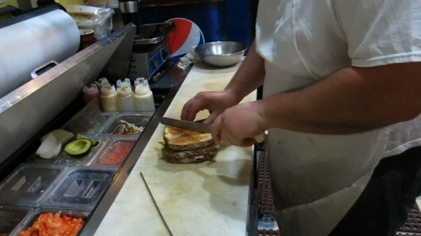 A cook slices a sandwich in the kitchen at Vittles in Pittsfield.