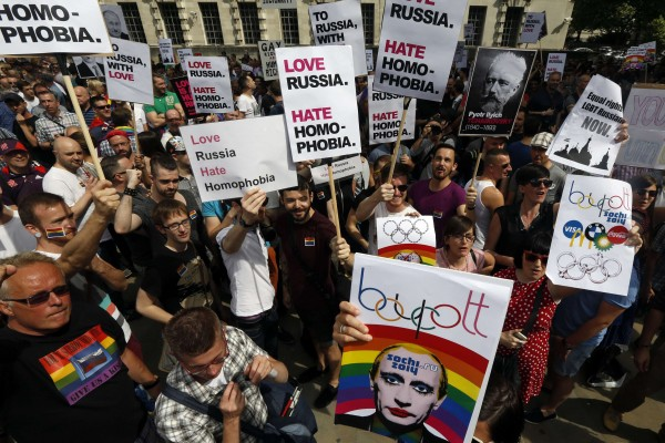 Demonstrators hold up signs, including one of Russia's President Vladimir Putin, during a protest against Russia's new anti-gay propaganda law, outside Downing Street in central London August 10, 2013.