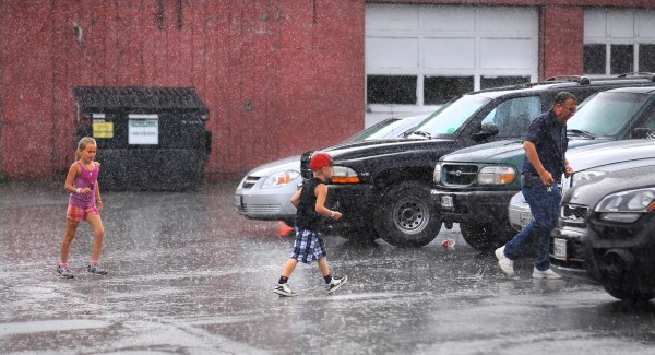 People rush to their vehicles from the Bangor State Fair as a downpour hit the region Saturday afternoon. The sunshine returned within an hour.