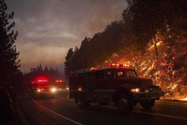 Fire trucks drive along Highway 120 while fighting the Rim Fire near Buck Meadows, Calif., on Saturday.