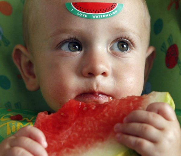 Braxton Krol, 14 months, enjoys a free slice of watermelon at the N.C. State Farmer's Market in Raleigh, Thursday, August 2, 2012.