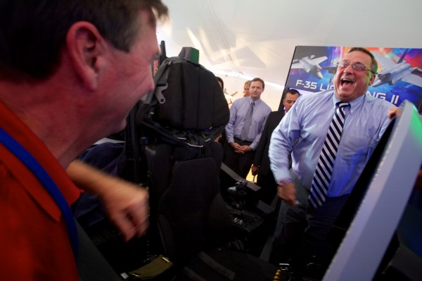 Governor Paul LePage laughs as Gary Hentz of Lockheed Martin gives him a set of plastic wings after the governor flew an F-35 Lightning II simulator at a Pratt & Whitney employee appreciation event in North Berwick Friday morning. The Pratt & Whitney facility manufactures the F-35's engine.