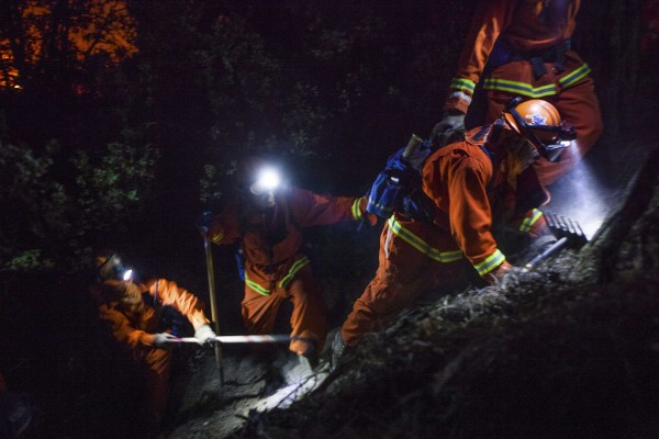 The McCain inmate crew out of San Diego struggles to cut a fire line on a steep slope on the Rim Fire near Buck Meadows, Calif., on Saturday.