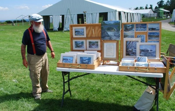 Kris Kristiansen has been selling his oil paintings since early May near Portland Head Light at Fort Williams Park in Cape Elizabeth. He does not want to move to a new, town-sanctioned site near a parking lot.