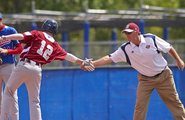 Maine District 3 coach Paul Huston of Bangor congratulates runner Dennis Farnham III on first base against Team Canada in the sixth inning of the opening game of the Senior League World Series on Sunday, August 11, 2013 at Mansfield Stadium in Bangor.