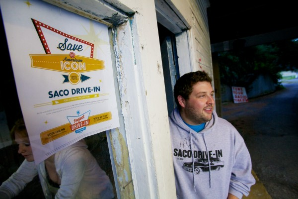Ry Russell, 23, owner of the Saco Drive-In theater gets the ticket booth ready with Corinne Ericson Tuesday. The theater is the second-oldest operational drive-in in the country and Russell hopes to keep it going next year by winning a contest that will get him a new digital projector.