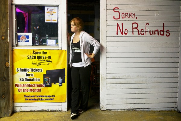 Corinne Ericson waits for the next carload at the Saco Drive-In theater's ticket booth Tuesday night. The owners of the drive-in, which first opened in 1939, are trying to win a national contest that will get them a brand new digital projector, allowing them to open next season.