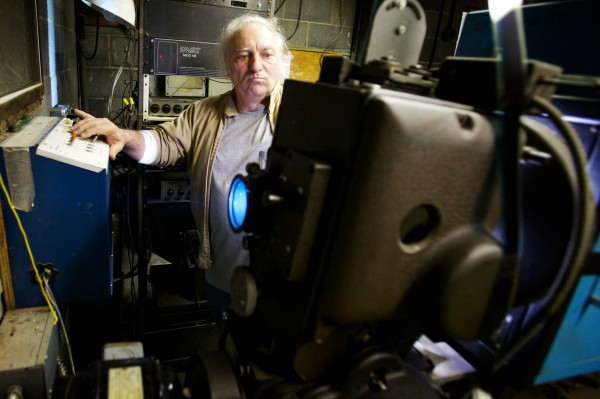 Projectionist Richard Julio operates the projector at the Saco Drive-In theater Tuesday night. The owners hope to keep it going next year by winning a contest that will get him a new digital projector, eliminating the need for film or a projectionist.