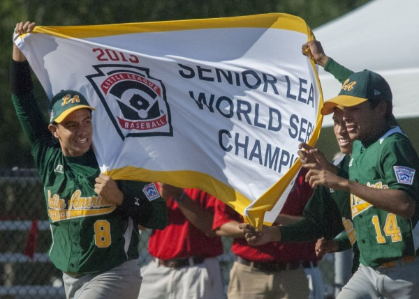 Team Latin America players Abel Frias (8) and Francisco Perez (14)  carry the championship banner around third base in celebration of their team's win in the Senior League World Series championship game at Mansfield Stadium in Bangor, Maine, Saturday August 17, 2013.