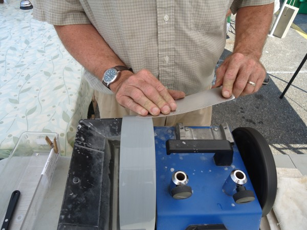 David Orbeton works on a wet wheel sharpener at the Falmouth Farmer's Market.