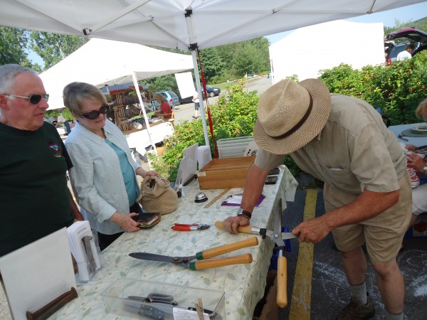 David Orbeton of Wicked Sharp works on hedge clippers as customers Rob and Luann Lawler of Cumberland Foreside wait at the Falmouth Farmers Market.