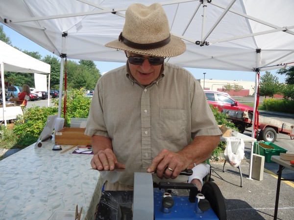 David Orbeton of Wicked Sharp hones a kitchen blade on a wet wheel sharpener at the Falmouth Farmers Market.