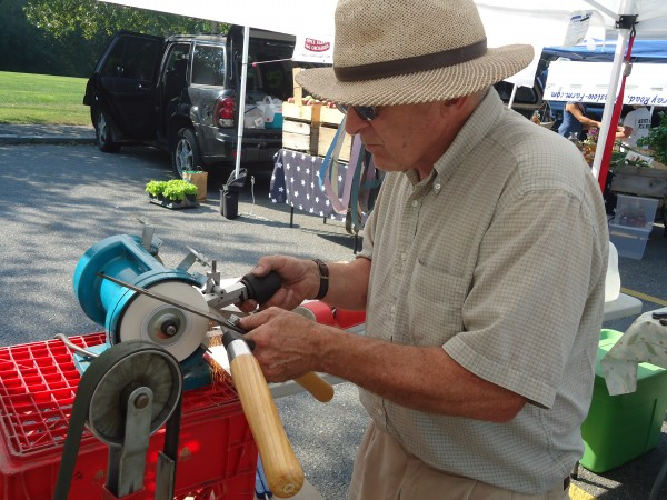 David Orbeton of Wicked Sharp works on a pair of hedge clippers at the Falmouth Farmers Market.