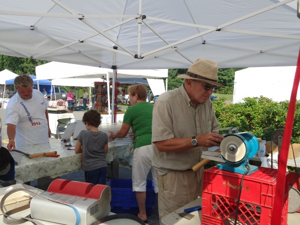 David Orbeton of Wicked Sharp gives people their edge back while they shop at the Falmouth Farmers Market.
