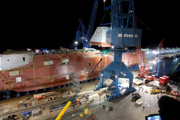 The 900-ton composite deckhouse of the DDG 1000 warship under construction at Bath Iron Works is hoisted onto to the hull of the ship in this 2012 file photo.