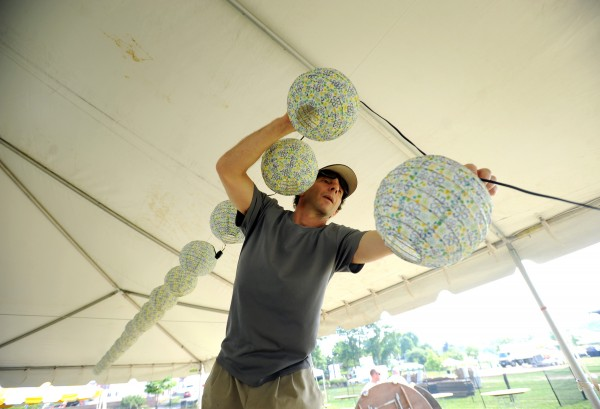 Lee Clein hangs party lights in a beer tent on Thursday morning. Clein volunteers every year for the American Folk Festival and this year he is helping with setup.