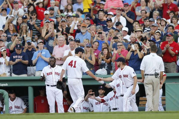 Boston Red Sox pitcher Ryan Dempster (46) welcomes pitcher John Lackey (41) to the dugout after being relieved during the seventh inning against the New York Yankees at Fenway Park in Boston Saturday.