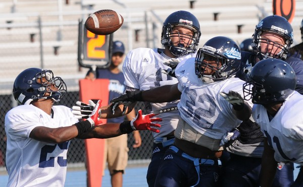 UMaine's No. 29, Najee Goode, and No. 32, Randy Samuels, along with a host of other UMaine players, break up a play during the Blue-White scrimmage on Tuesday at Morse Field on the UMaine campus in Orono.