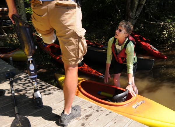 Brian Miller of York, Pa., removes his prosthetic leg as Sara Stockwell of Maine Adaptive Sports and Recreation steadies a kayak at Camp Wavus in Jefferson on Saturday during a veterans retreat offered by Veterans No Boundrie