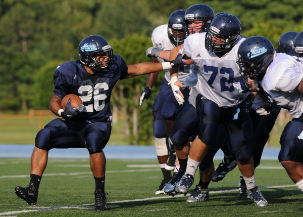 The University of Maine's Nigel Jones fends off defensemen as he runs the ball during a Blue-White scrimmage on Tuesday at Alfond Stadium in Orono.