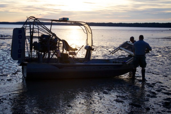 Clammer and volunteer Chris Green (left) and Brunswick Marine Resources Officer Dan Devereaux load up an airboat at the Freeport end of Maquoit Bay Friday morning around low tide with materials to build crab exclusion pens.