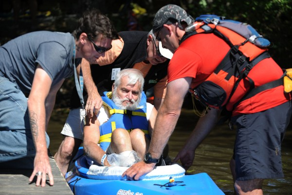 Dave St. Hilaire (from left) helps Bob Kroll and Mike Henry as they put disabled veteran George St. Hilaire (center) into his kayak after Henry made a custom seat to assist with St. Hilaire's balance and comfort out on the water.