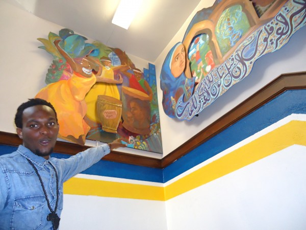 Portland High School incoming senior Quentin Ndayishimiye of Africa points out the mural he worked on that represents genocide in Burundi and Rwanda. &quotWith Eyes in our Hearts&quot was unveiled Tuesday.