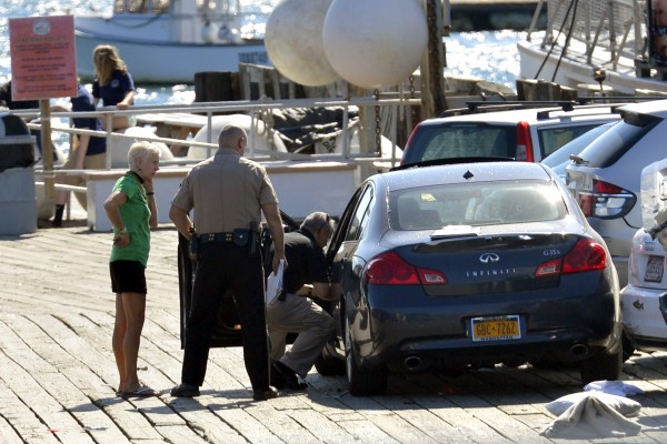 Driver Cheryl Torgerson (from left), Knox County Sheriff's Sgt. John Palmer and Lt. Kirk Guerette look over the car that Torgerson was driving after she allegedly lost control, struck several cars and a family, killing a 9-year-old boy, Sunday afternoon at the Monhegan Boat Landing in Port Clyde.