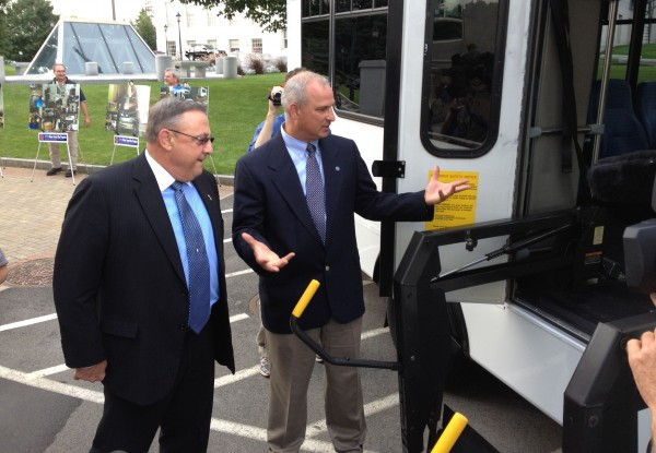 Gov. Paul LePage takes a look at a refurbished bus with Tim McCabe, director of Business Development for Maine Military Authority, who unveiled the product of his company's transit rehabilitation program at the State House on Wednesday.