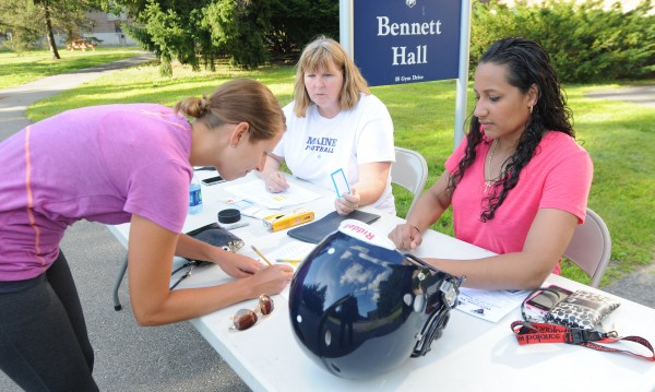 Lindsay Archer, left, of Bangor signs up for Football 101 for Women at the University of Maine on Thursday. Women were taught the rules of football along with a tour of the UMaine football facility.