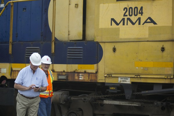 Robert Grindrod (left), president of the Montreal, Maine and Atlantic Railway, took photographs where a dump truck collided with a train Thursday morning on Western Avenue in Hampden.