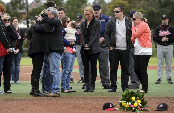 Peter and Donna Lane, parents of murdered Australian Christopher Lane, embrace as other family members and Christopher's girlfriend Sarah Harper (center, in black) look on, during a memorial service on August 25, 2013. Lane, 23, who played baseball at the Melbourne club, was found dead of a gunshot wound on August 23, 2013, according to police in Duncan, Oklahoma.