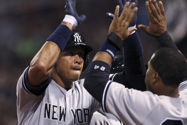 New York's Alex Rodriguez (left) celebrates his solo home run in the sixth inning against the Boston Red Sox Sunday night at Fenway Park in Boston. The Yankees won 9-6.