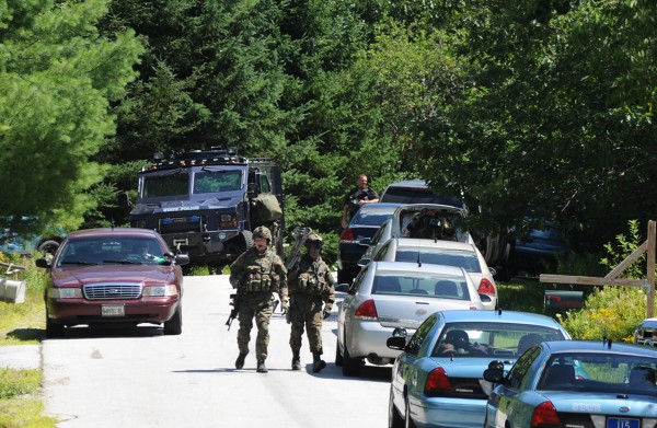 The Maine State Police tactical team walks down Peakes Hill Road in Dedham after looking for William Morse at a nearby home on Thursday.