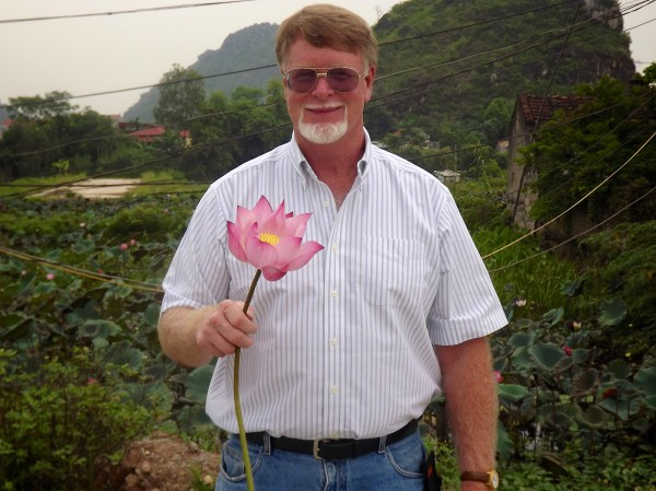 Jeff Wheeler holds a lotus flower in Ninh Binh province of Vietnam. Wheeler traveled to Thailand for shoulder surgery and saved enough money in the process to combine it with a sightseeing trip.