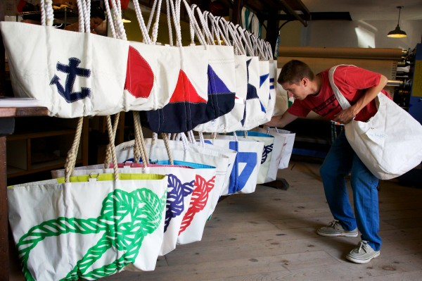 Rob McCarthy straightens out the merchandise at Sea Bags on Customs House Wharf in Portland Wednesday. The company, which makes products from recycled sails, is expanding from 1,500 square feet to 4,500 square feet on the wharf.