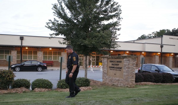 A policeman walks in front of McNair Discovery Learning Academy after a shooting incident in Decatur, Georgia, August 20, 2013. Police arrested a 20-year-old man on Tuesday for opening fire with an AK-47 inside an elementary school in the Atlanta suburbs, forcing the evacuation of 800 students who were all reunited with their parents without injury, officials said.