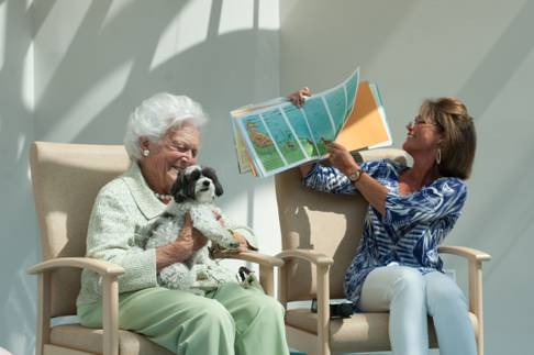 Former first lady Barbara Bush visited the children's hospital that bears her name at Maine Medical Center in Portland on Aug. 22, 2013. Her daughter-in-law, Margaret Molster Bush, right, reads to a group of children as Tess, a Maltese-poodle mix, sits on Barbara Bush's lap.