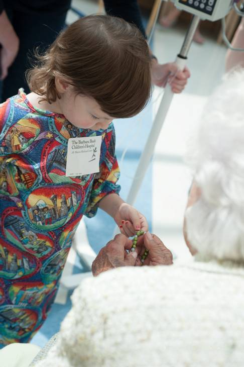 Three-year-old Avery Garrison of Scarborough examines a bracelet given to her by former first lady Barbara Bush.