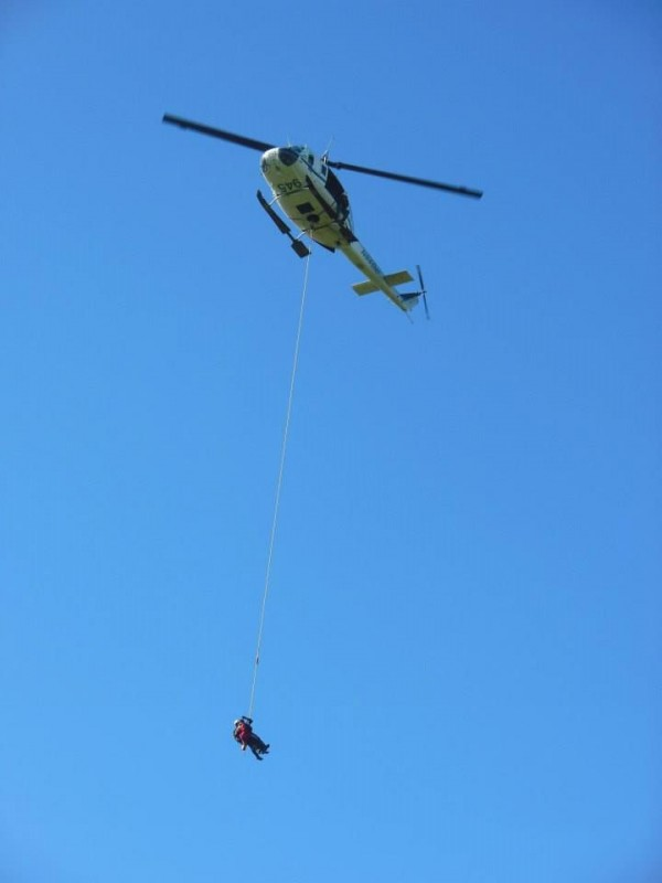Maine Forest Service helicopter airlifts man suffering symptoms of a diabetic stroke from a point on the Bold Coast Trail to Cutler; the man and a forest ranger rescuer are suspended beneath the helicopter.