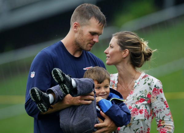 Tom Brady of the New England Patriots walks with his son, Benjamin, and wife, Gisele, after a joint practice with the Tampa Bay Buccaneers in Foxborough, Massachusetts, on Tuesday, August 13, 2013.