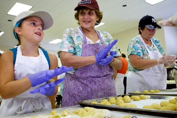 Sophia Lambert, 9, shapes cookies with MaryAnne DiSanto (center) and Shirley Blodgett Wednesdat at St. Peter's Church in Portland for this weekend's 88th annual Italian Bazaar, commemorating the Feast of St. Rocco.