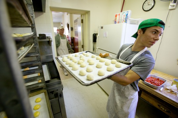 Angelo Magno carries a tray of unbaked cookies Wednesday at St. Peter's Church in Portland as volunteers bake in advance of this weekend's 88th annual Italian Bazaar.