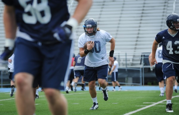 UMaine tight end Justin Perillo runs through drills with his teammates on Morse Field during the first practice of the season Monday.