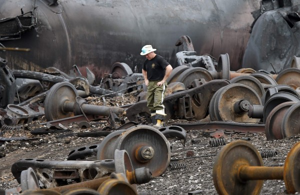 A police officer walks past axle gear in Lac-Megantic, Quebec in this July 9, 2013 file photo. Montreal, Maine and Atlantic, the railway involved in last month's deadly derailment in Lac-Megantic, Quebec, filed for Chapter 11 bankruptcy protection on August 7, 2013,