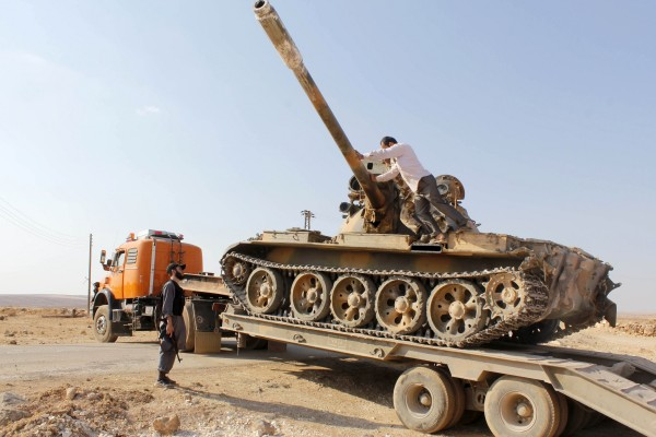 Free Syrian Army fighters drive a military tank that belonged to forces loyal to Syria's President Bashar Al-Assad after they seized it, in Aleppo's town of Khanasir August 29, 2013.
