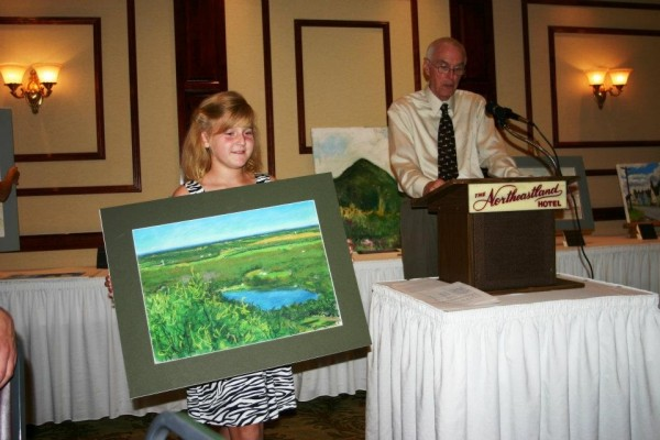 Paige McHatten shows a painting by Frank Sullivan of Littleton during a previous Presque Isle fresh paint auction as University of Maine at Presque Isle President Donald Zillman seeks bids from the audience.