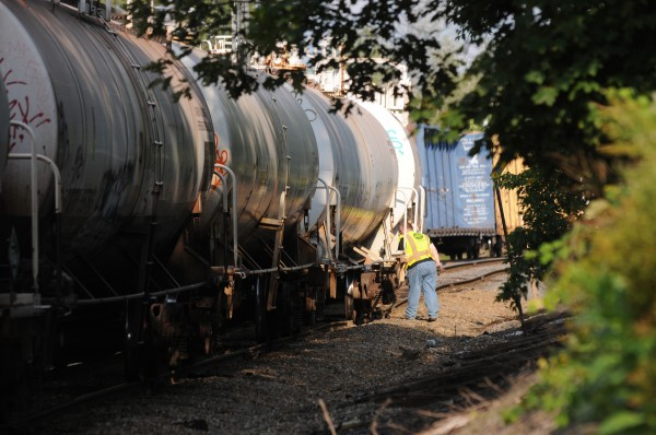 A Pan Am Railways worker looks at rail cars along a section of track near the Coldbrook Road in Hermon on Monday.