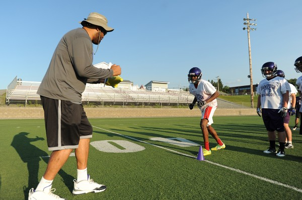 Hampden Academy head football coach Kevin Canty, left, works with Isaiah Bess (center) during Hampden Academy's first football practice of the season at Hampden Academy on Monday.