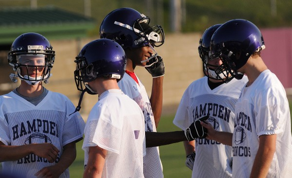 Isaiah Bess meets some of his new football teammates during Hampden Academy's first football practice of the season at Hampden Academy on Monday.